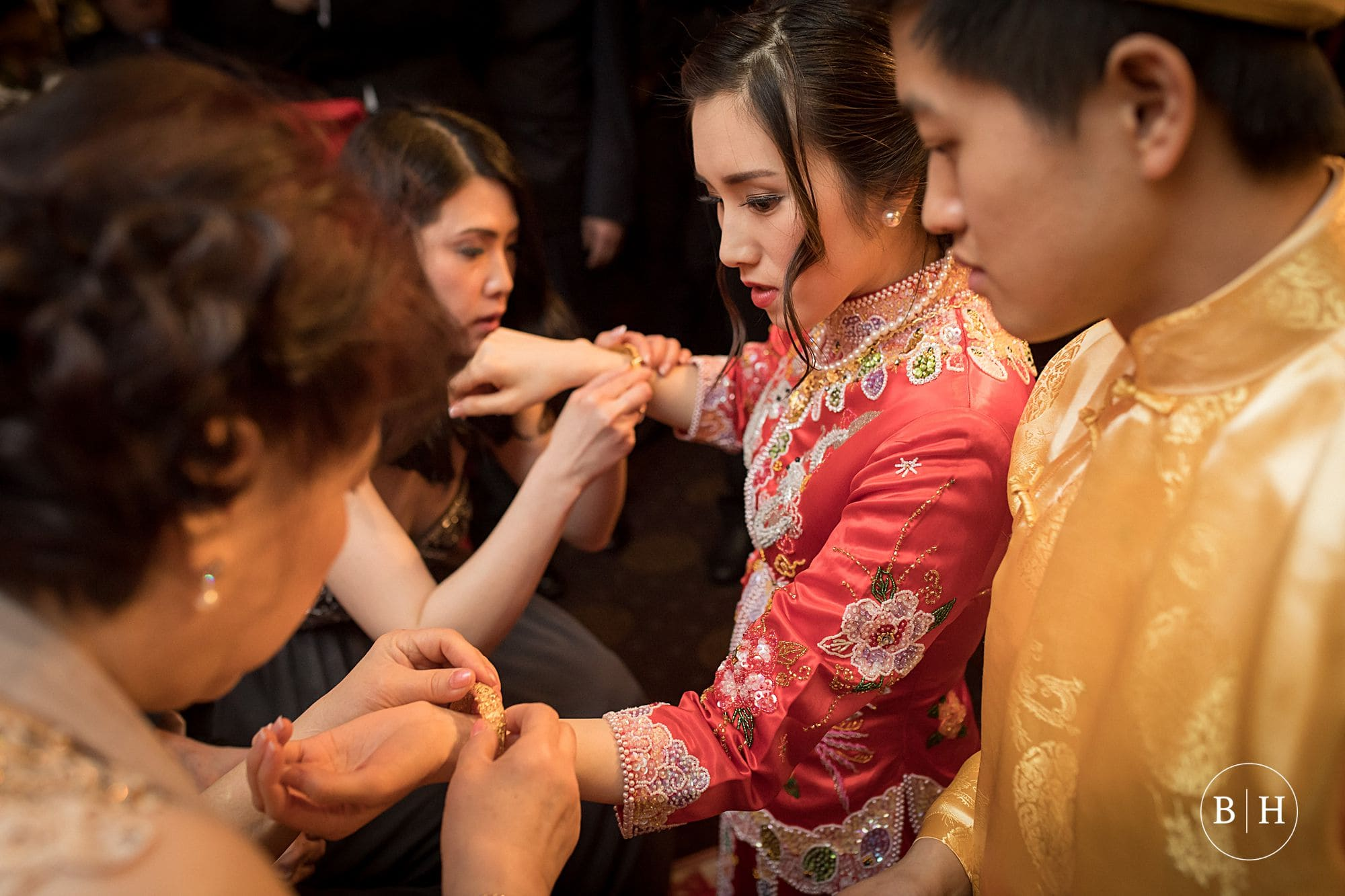 Bride in traditional dress receiving gold jewellery at Chinese Tea Ceremony