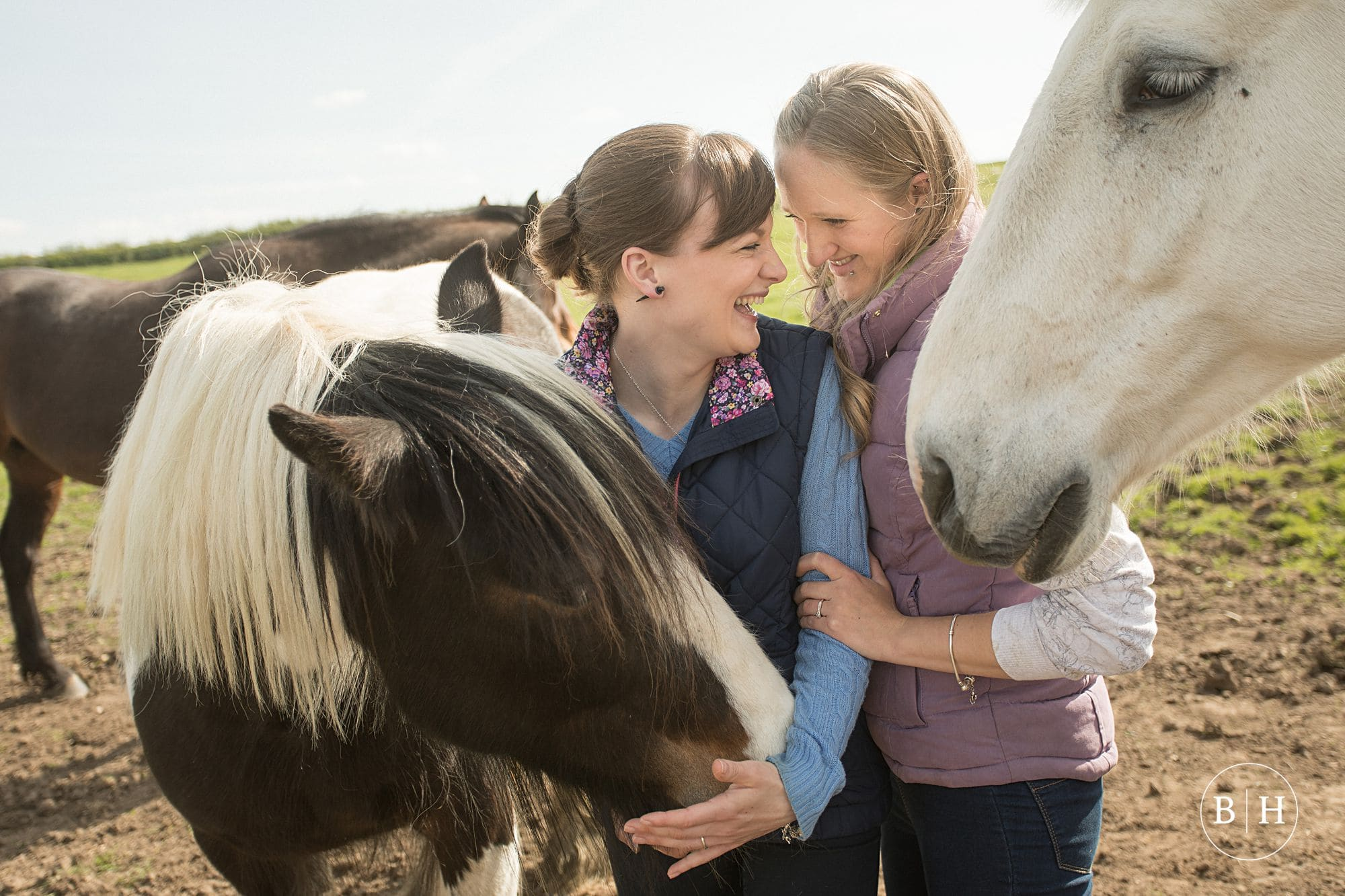 Couple with horses on Farmyard Engagement Shoot