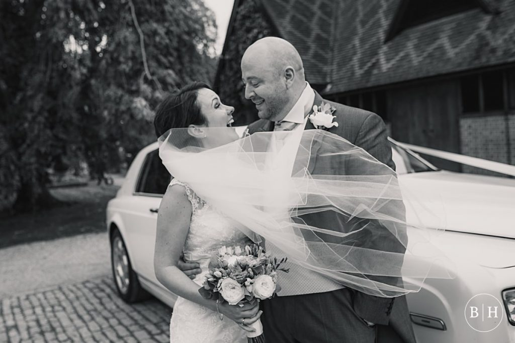 Wedding couple with veil blowing in the wind at Waddesdon Dairy in Buckinghamshire. Taken by Becky Harley Photography