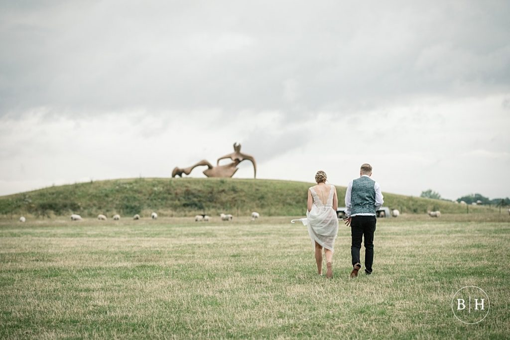 Bride and Groom walking towards Henry Moore's reclining figure taken by Becky Harley Photography