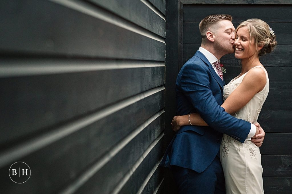 Groom kissing bride at Moreton Walled Garden in Dorset, taken by Becky Harley Photography