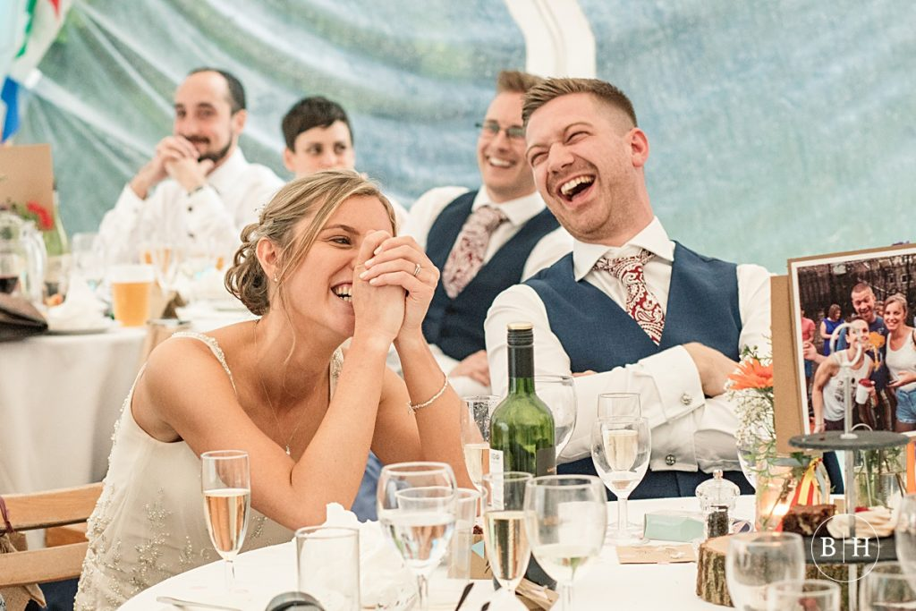 Bride and groom laughing at speeches, taken by Becky Harley Photography