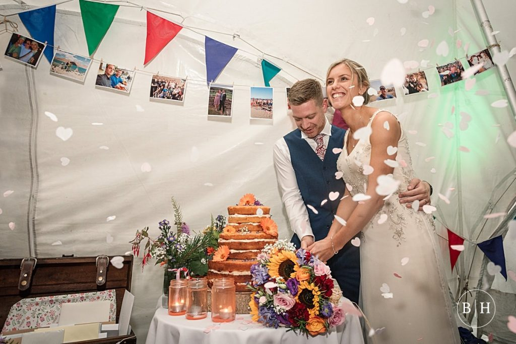 Bride and groom cutting the wedding cake at Moreton Walled Garden, taken by Becky Harley Photography