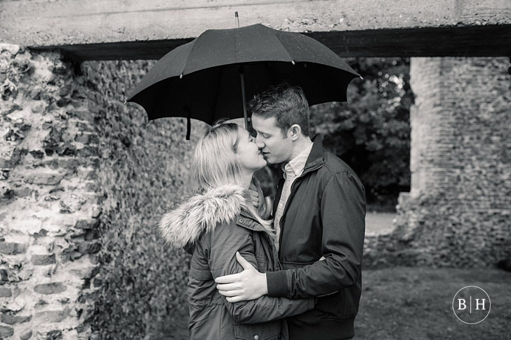Engaged couple kissing under an umbrella at Sopwell Nunnery in St Albans taken by Becky Harley Photography
