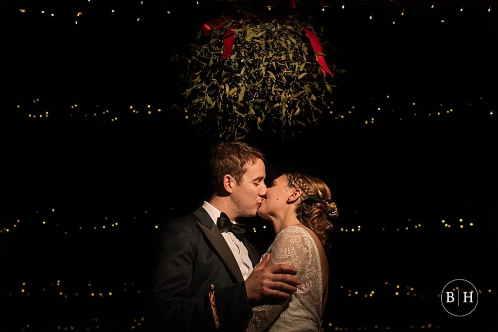 Bride and Groom under the mistletoe, at a Winter Milling Barn wedding aken by Becky Harley Photography