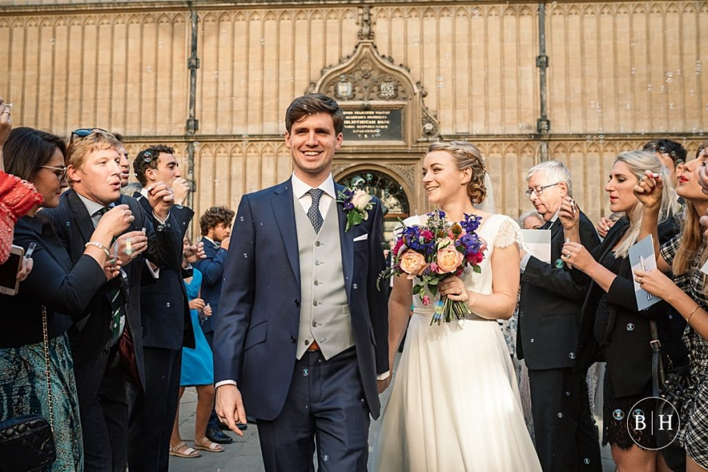 Bride and Groom with bubble confetti at Bodleian Library Wedding taken by Becky Harley Photography