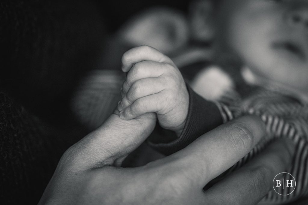 Newborn baby hand with dad taken by Becky Harley Photography