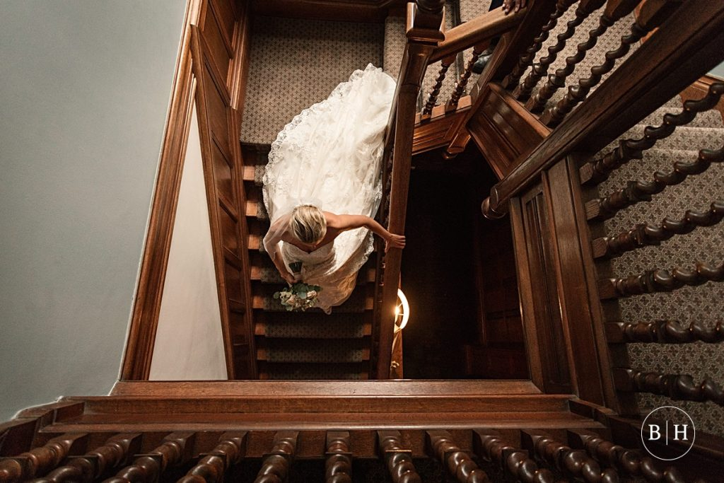 Bride coming down staircase at Pendrell Hall taken by Becky Harley Photography