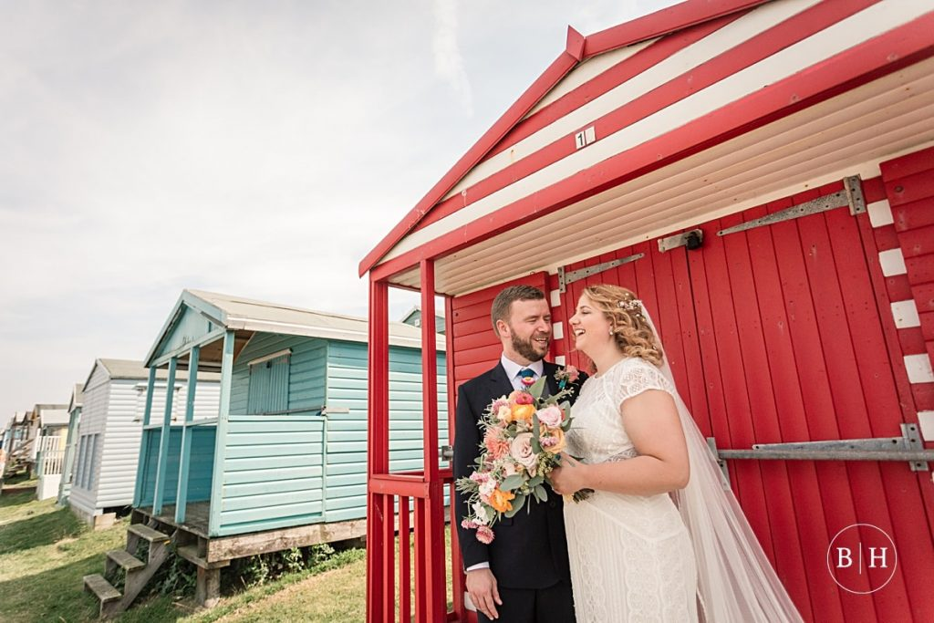 Bride and groom by colourful red beach house at Whitstable Wedding taken by Becky Harley Photography