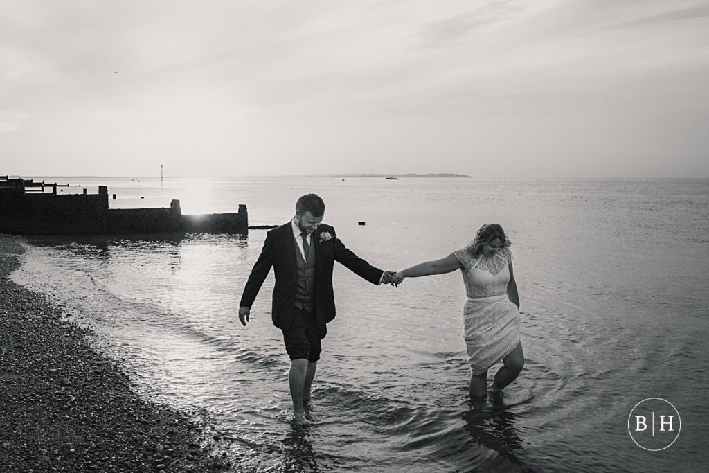Bride and groom paddling in the sea at Whitstable Wedding taken by Becky Harley Photography