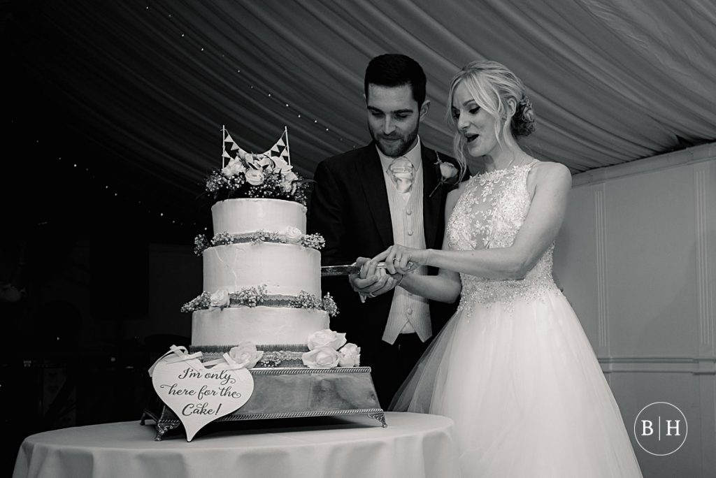 bride and groom cutting wedding cake Riverside marquee wedding taken by Becky Harley Photography