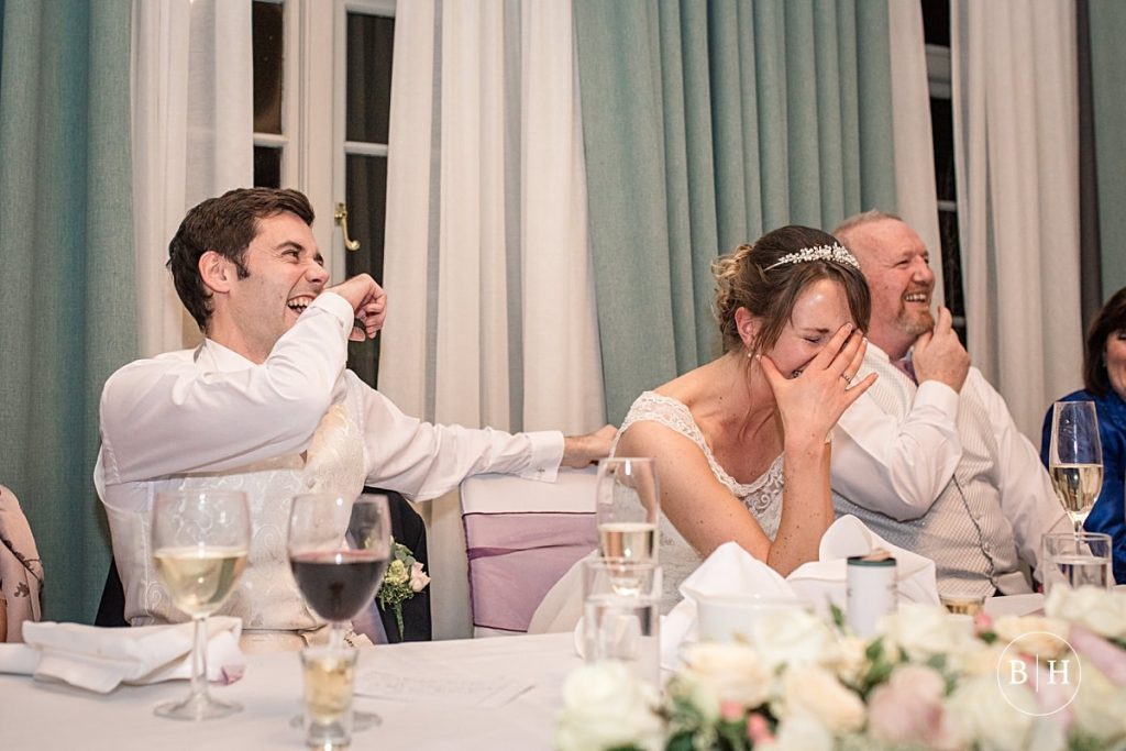 bride and groom react to speeches at Theobalds Estate Wedding taken by Becky Harley Photography