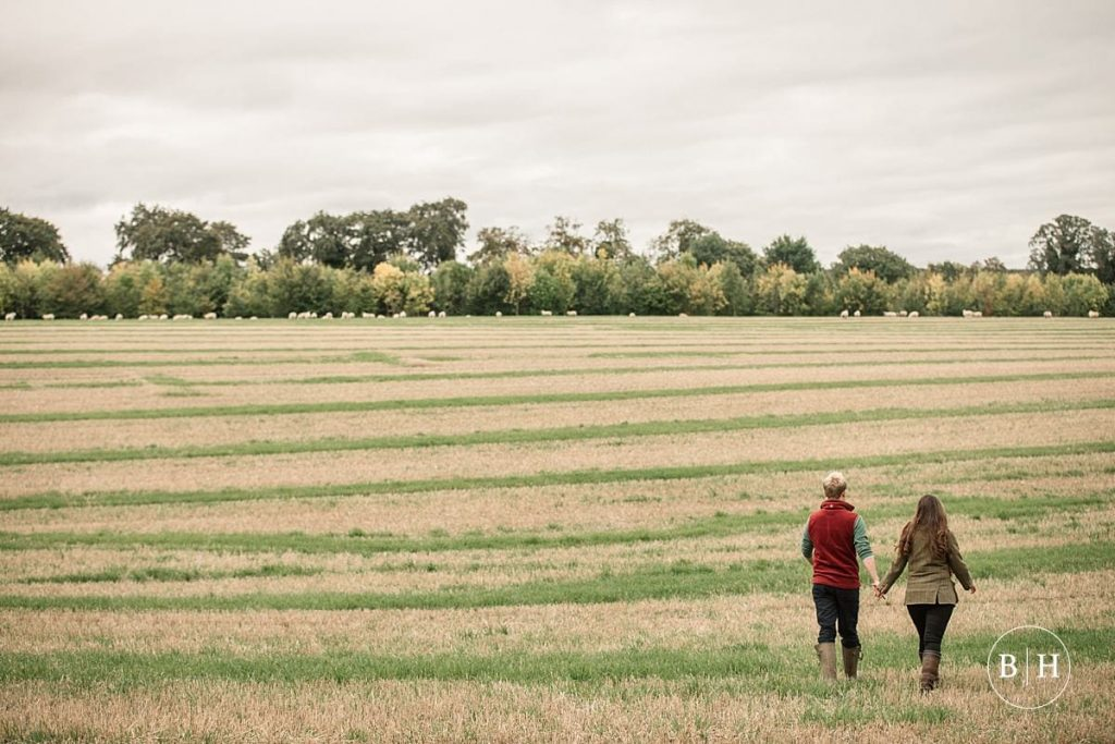engaged couple walking in a field taken by Becky Harley Photography