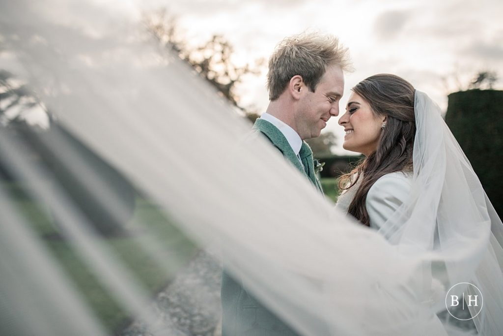 Bride and Groom at Hengrave Hall behind veil, taken by Becky Harley Photography