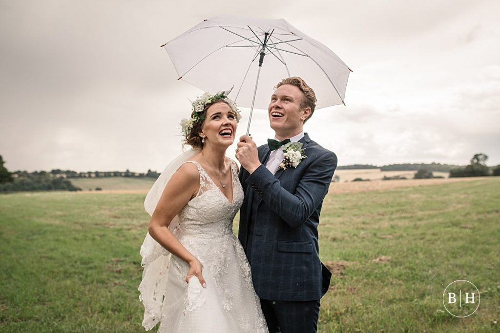 bride and groom with umbrella at Offley Place Wedding taken by Becky Harley Photography