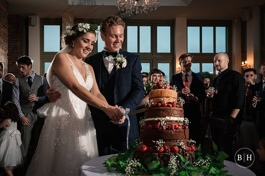 bride and groom cutting cake at Offley Place Wedding taken by Becky Harley Photography