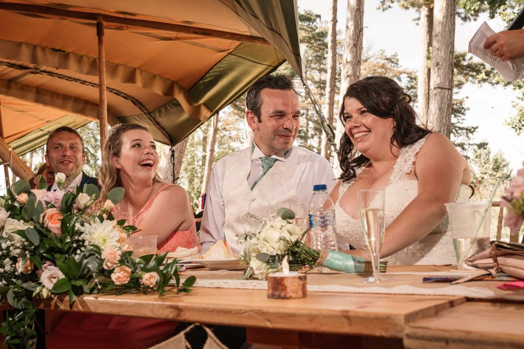 Bride and groom reacting to speeches at Brook Farm Cuffley Wedding taken by Becky Harley Photography