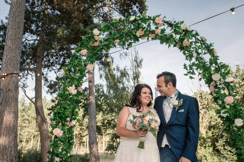 Bride and groom with flower arch at Brook Farm Cuffley Wedding taken by Becky Harley Photography
