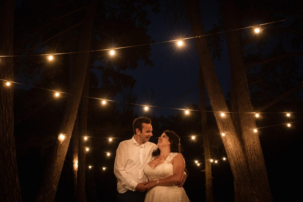 Bride and groom with festoon lighting at Brook Farm Cuffley Wedding taken by Becky Harley Photography