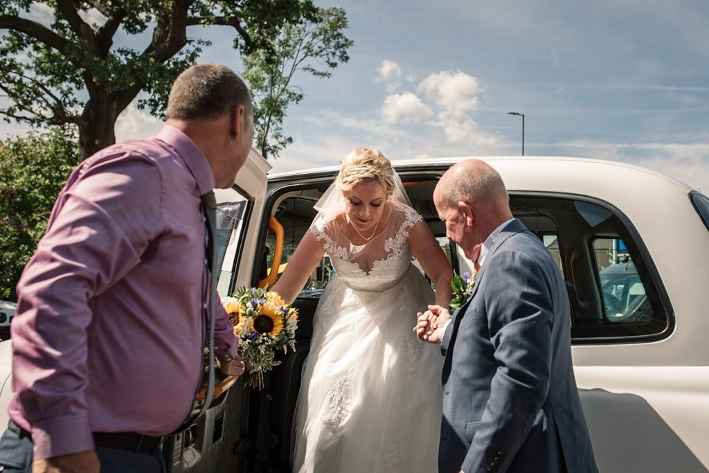 Bride arriving in white taxi at summer Milling Barn wedding, taken by Becky Harley Photography