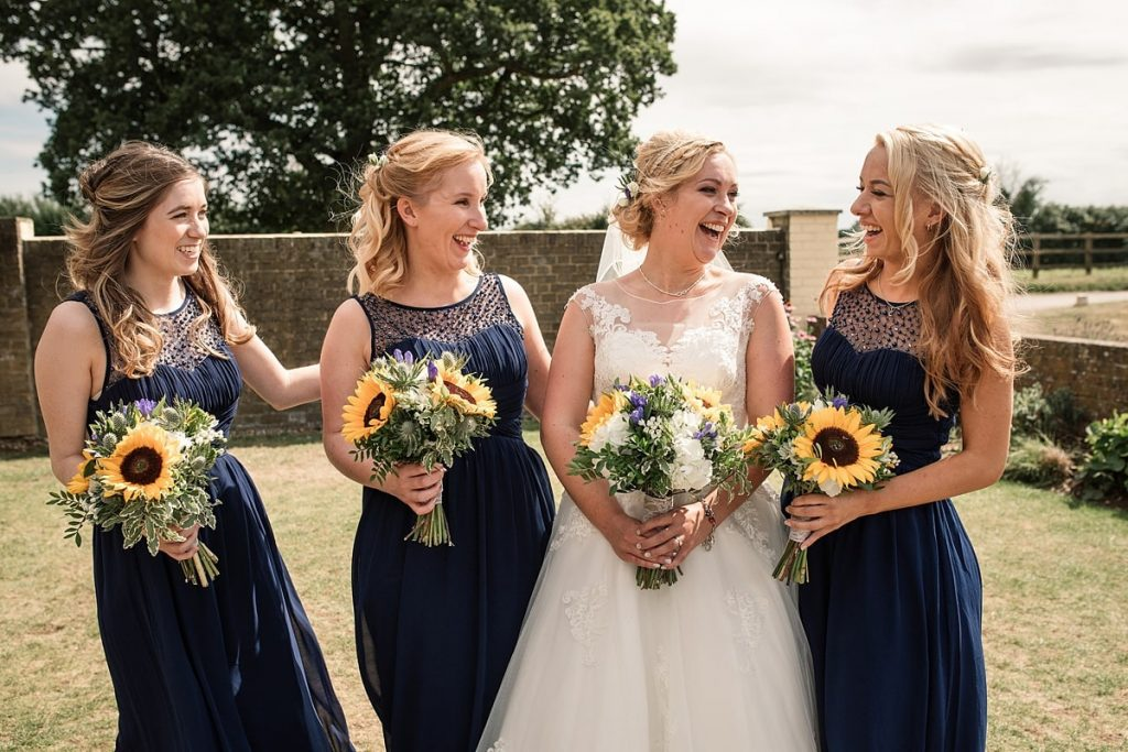 Bride and bridesmaids with sunflower bouquets at summer Milling Barn wedding, taken by Becky Harley Photography