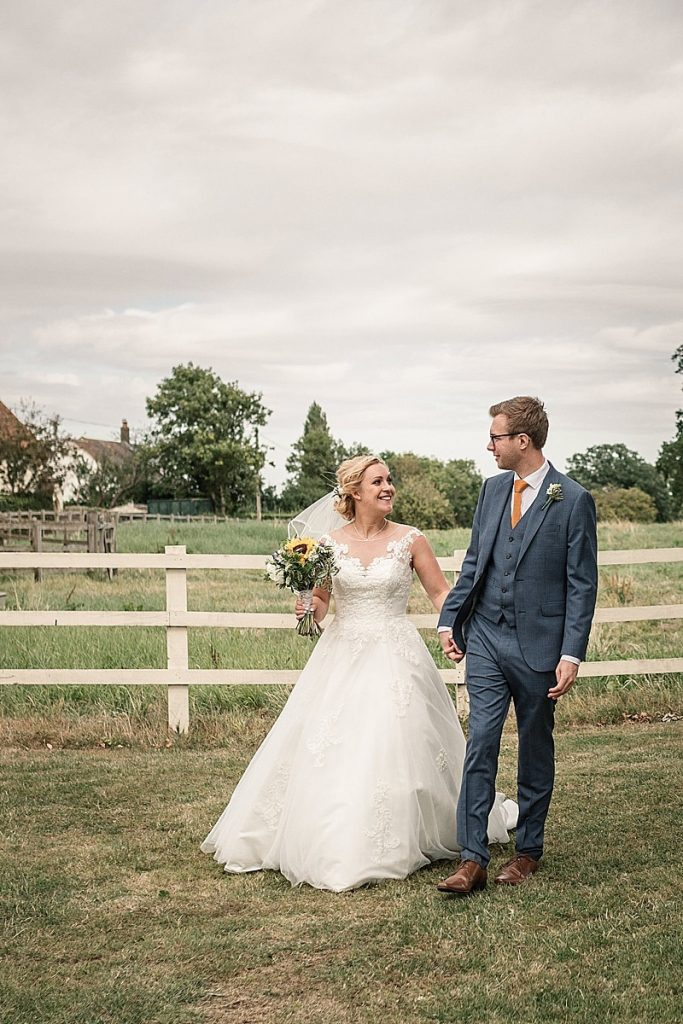 Bride and groom walking in the grounds of Milling Barn at summer Milling Barn wedding, taken by Becky Harley Photography