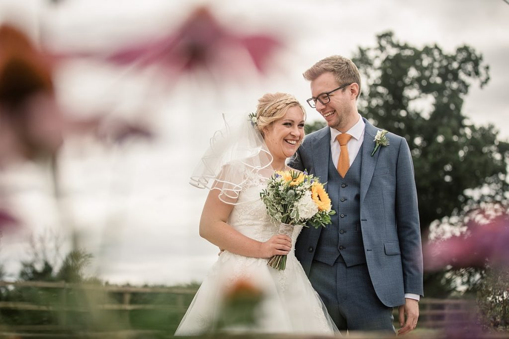 Bride and groom with flowers at summer Milling Barn wedding, taken by Becky Harley Photography