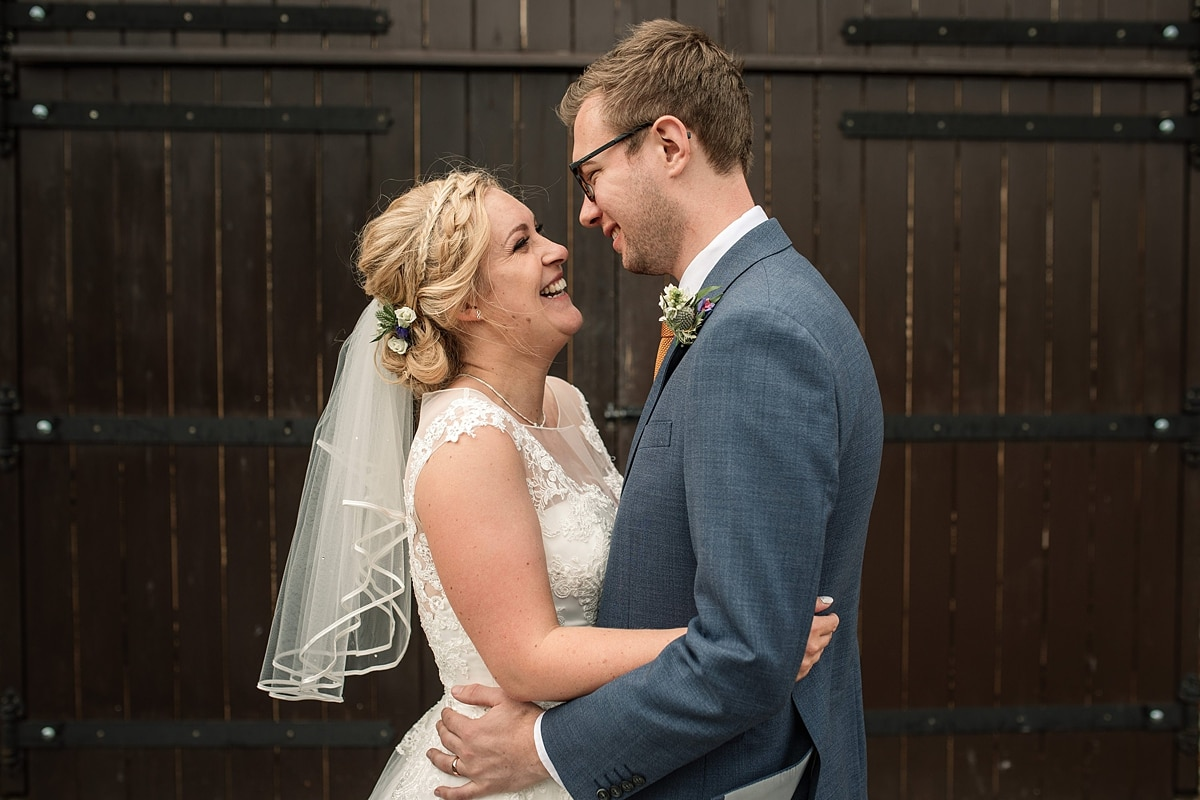 Bride and groom by barn door at summer Milling Barn wedding, taken by Becky Harley Photography