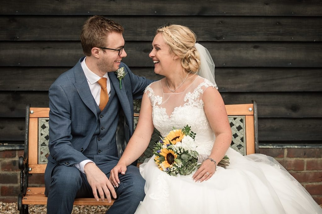Bride and groom seated on a bench at summer Milling Barn wedding, taken by Becky Harley Photography