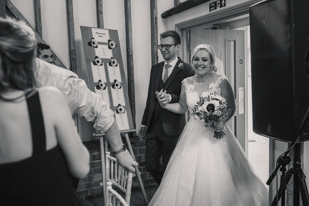 bride and groom entering wedding breakfast at summer Milling Barn wedding, taken by Becky Harley Photography