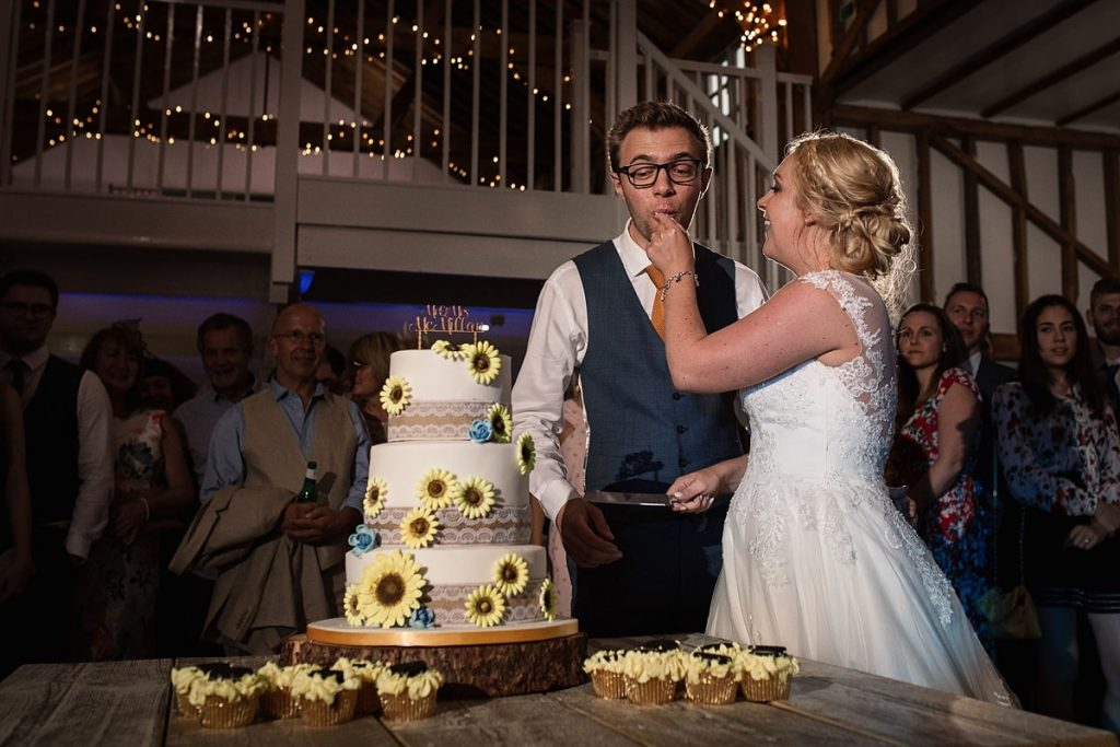 bride and groom cutting the cake at summer Milling Barn wedding, taken by Becky Harley Photography