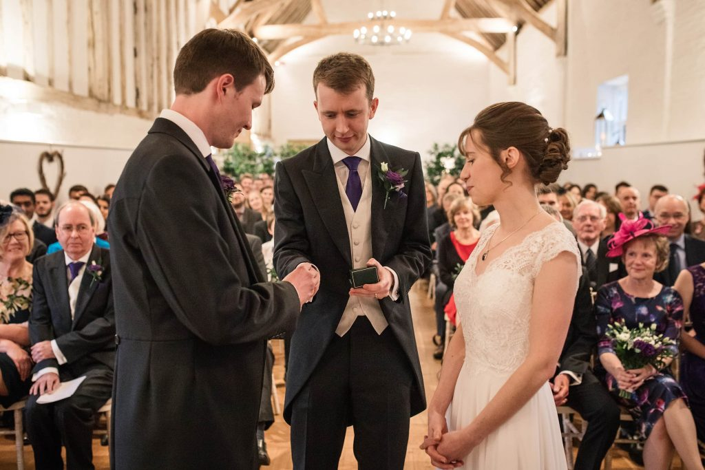 Best man handing over wedding rings to groom at Alswick Barn wedding in Buntingford, taken by Becky Harley Photography