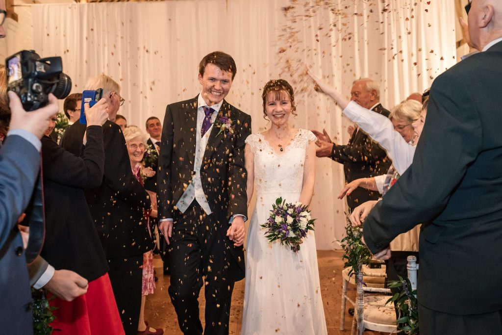 Bride and Groom with autumn leaf confetti indoors at Alswick Barn wedding in Buntingford, taken by Becky Harley Photography