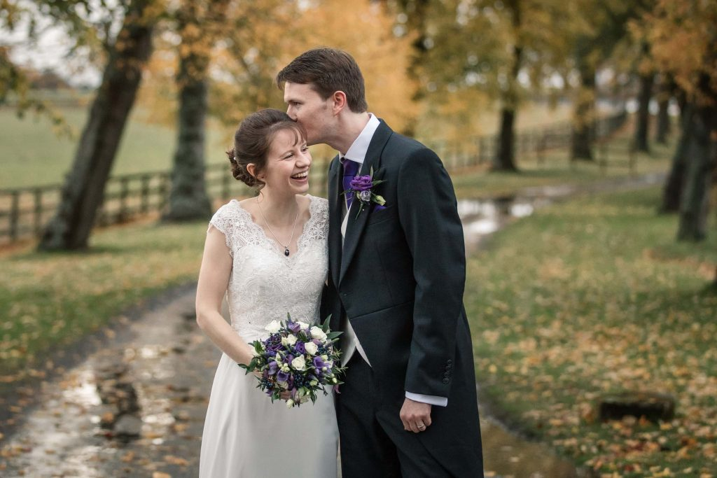 Bride and Groom on Alswick driveway with autumn leaves at Alswick Barn wedding in Buntingford, taken by Becky Harley Photography