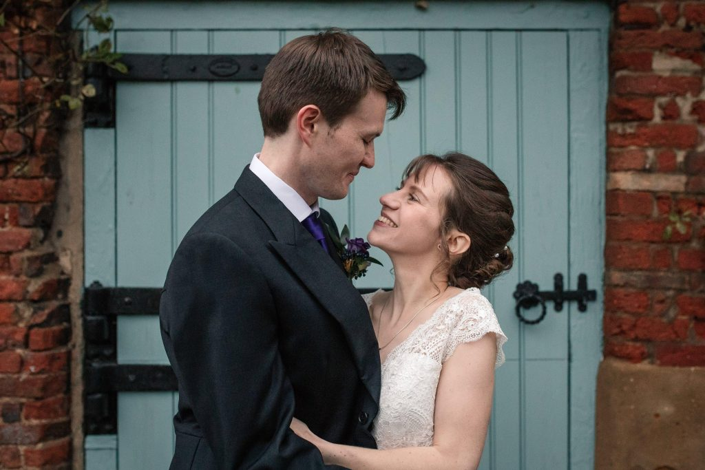 Bride and Groom in front of blue door at Alswick Barn wedding in Buntingford, taken by Becky Harley Photography