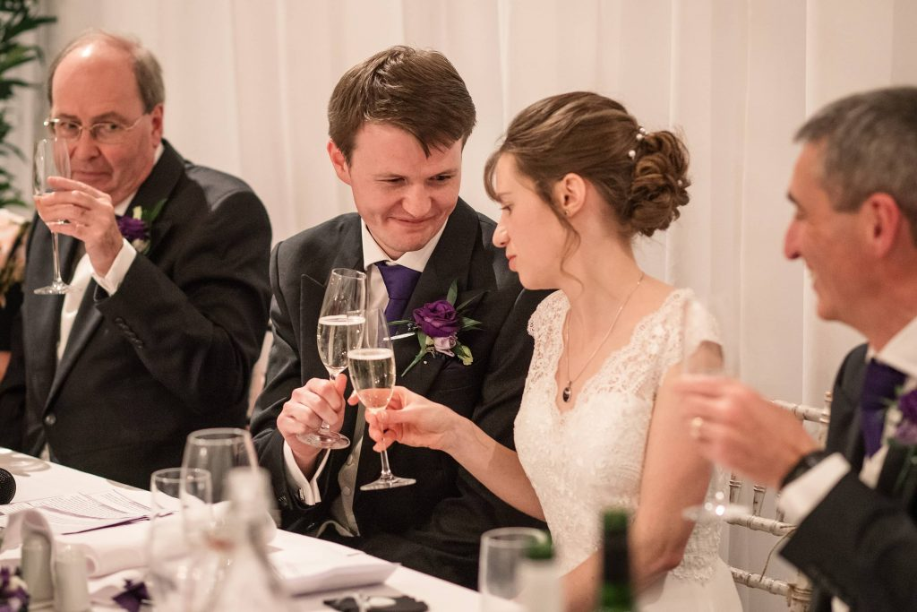 Bride and groom toasting with champagne at Alswick Barn wedding in Buntingford, taken by Becky Harley Photography