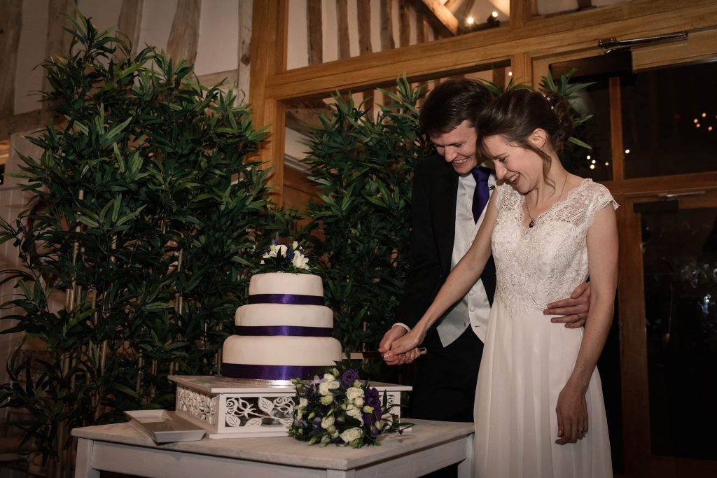 Bride and Groom cutting the cake at Alswick Barn wedding in Buntingford, taken by Becky Harley Photography