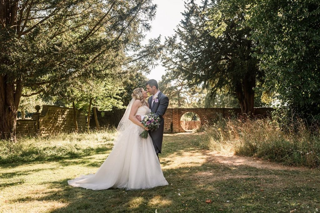 Bride and Groom in gardens at summer Fanhams Hall Wedding taken by Becky Harley Photography