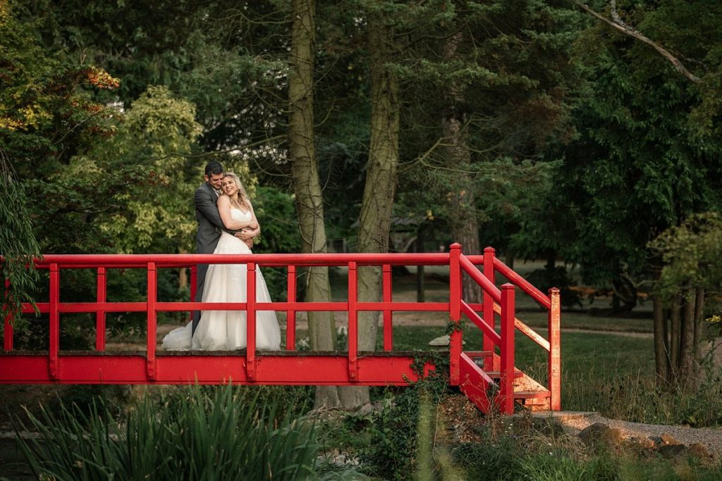 Bride and groom on red bridge at summer Fanhams Hall Wedding taken by Becky Harley Photography