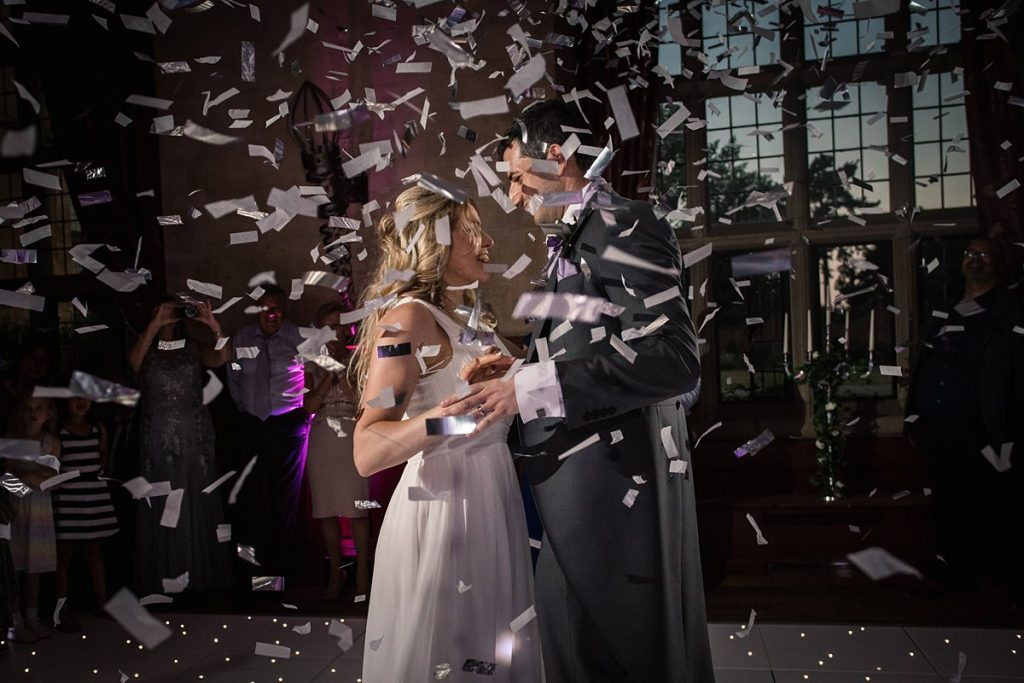 Bride and Groom with confetti canon at summer Fanhams Hall Wedding taken by Becky Harley Photography