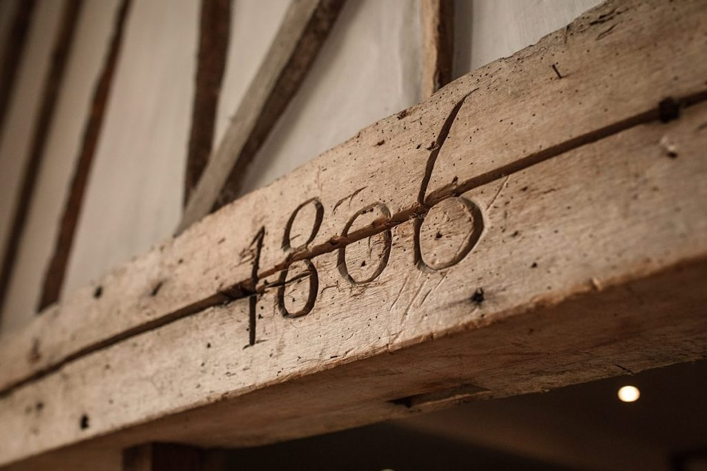 1806 carving in beam at Maiden's Barn Wedding taken by Becky Harley Photography
