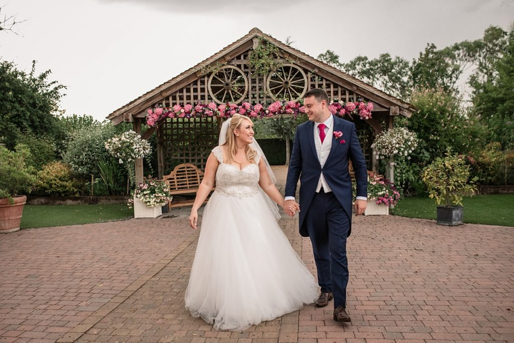 Bride and Groom with floral arch at Maiden's Barn in Essex taken by Becky Harley Photography