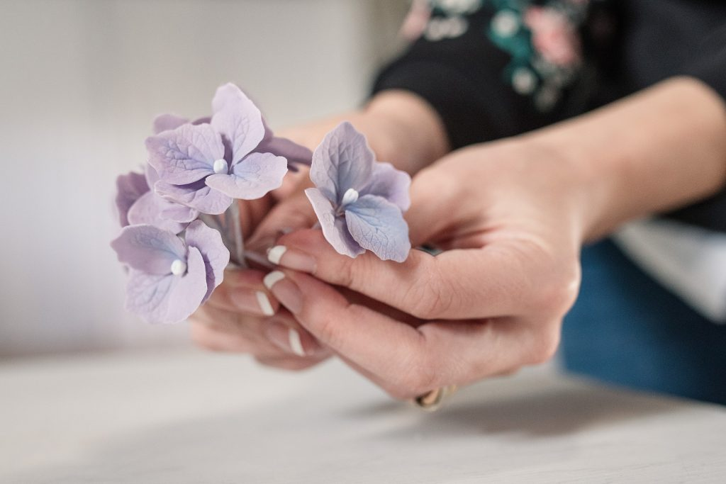 Nina from Meadowsweet Cakes making purple icing flowers, taken by Becky Harley Photography