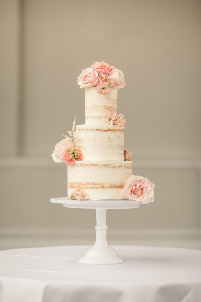 Luxury semi-naked wedding cake with fresh flowers by Meadowsweet Cakes, taken by Becky Harley Photography