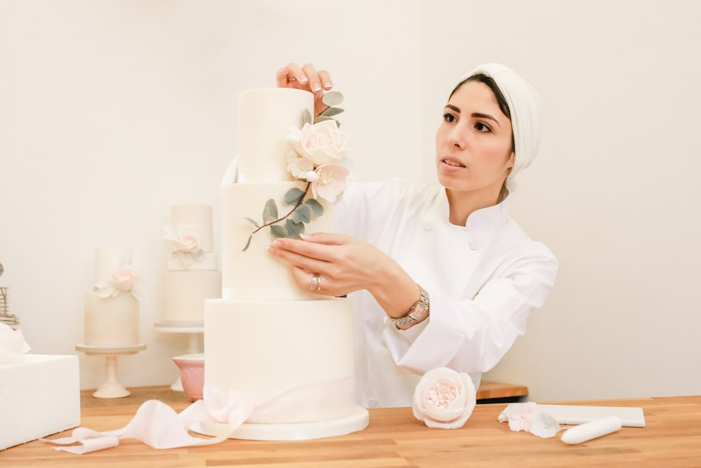 Nina from Meadowsweet Cakes decorating a cake, taken by Becky Harley Photography