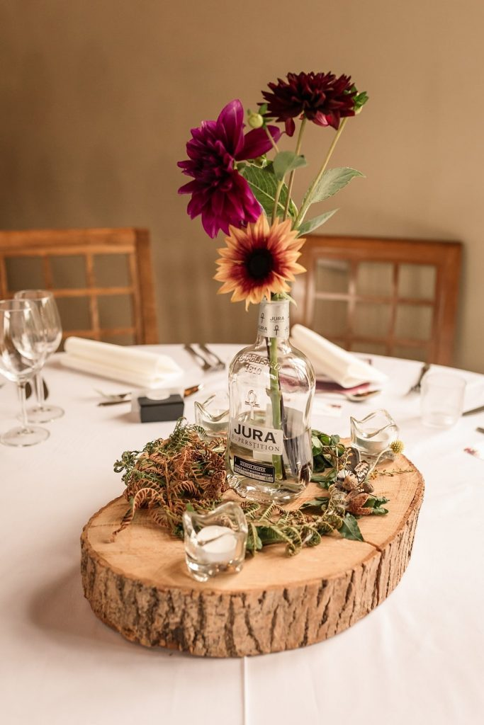 Wedding table centres in whisky bottles at Dodmoor House Wedding, taken by Becky Harley Photography