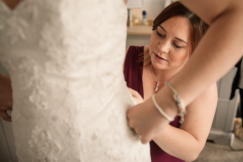 maid of honour doing up wedding dress before Offley Place Wedding, taken by Becky Harley Photography