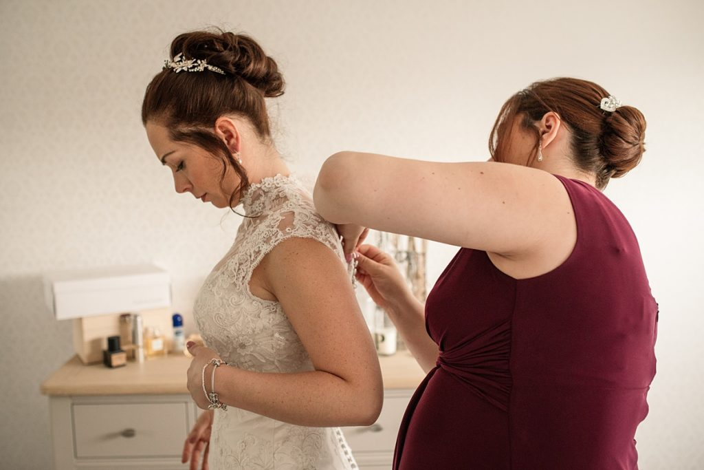 bride getting into wedding dress before Offley Place Wedding, taken by Becky Harley Photograph