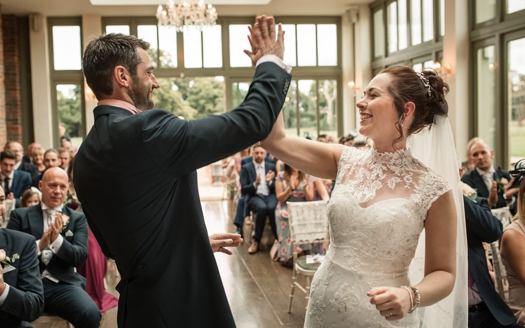 Bride and Groom high five during wedding ceremony at Offley Place Wedding, taken by Becky Harley Photography