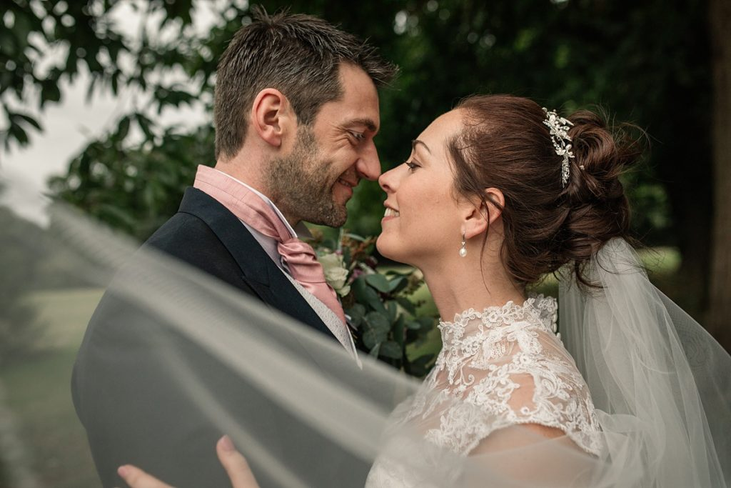 Bride and Groom with veil at Offley Place Wedding, taken by Becky Harley Photography